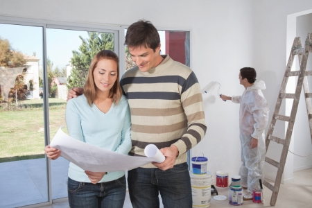 Couple going through house plan while painter in the background Stock Photo - 9887550
