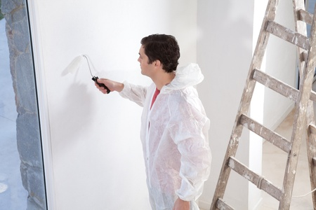 Painter painting the wall with roller photo
