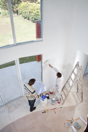 High angle view of man holding blueprint and workman painting the wall photo