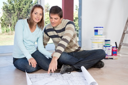 Mature couple sitting on the floor with blueprint of their new house photo