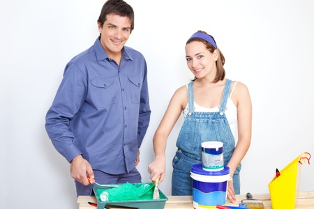 Portrait of happy couple with roller, paint and bucket on table photo