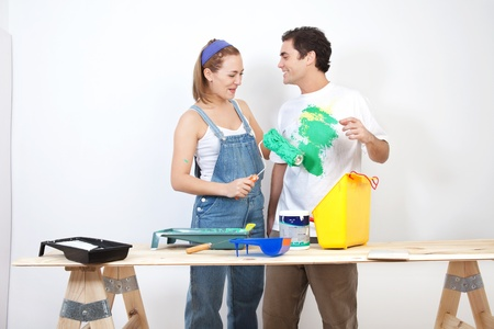 Smiling woman painting husband's t-shirt with roller Stock Photo - 9886935