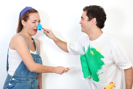 Young happy couple playing with paint against white background Stock Photo - 9887294