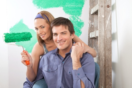 Beautiful young couple sitting together with color roller at home Stock Photo - 9887487