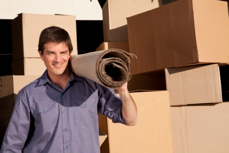 relocating: A moving an carrying a carpet with cardboard boxes in the background
