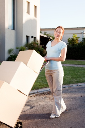 A woman with a stack of cardboard boxes on a trolly Stock Photo - 9887546
