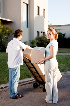 trolly: A happy moving couple with boxes on a trolly