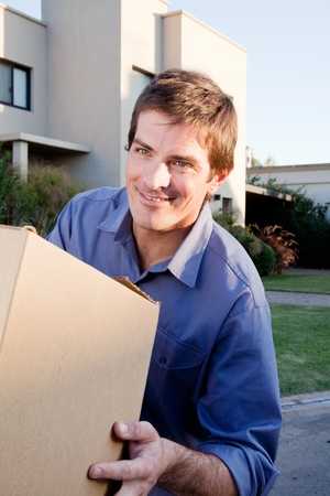 A happy man with a moving box in front of a house photo