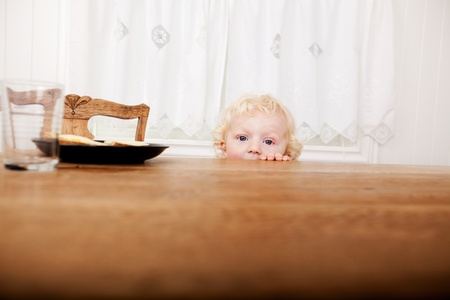 A young toddler peeking over the edge of the table before meal time photo