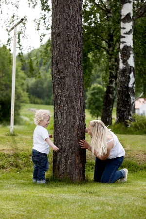 Mother and son playing hide and seek outdoors in a rural setting photo