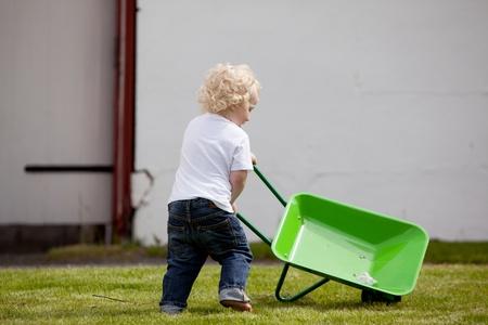 ni�o empujando: Un ni�o de corta edad empujando una carretilla