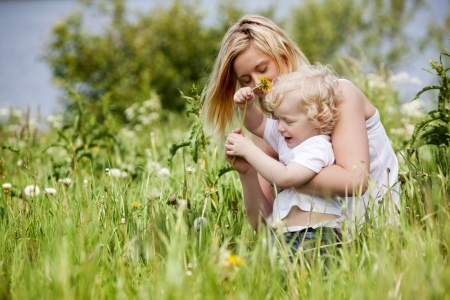 norwegian: A mother and son having fun playing with flowers in a grass field Stock Photo