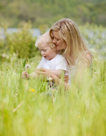 A mother and son making a wish on a dandelion in a green meadow photo