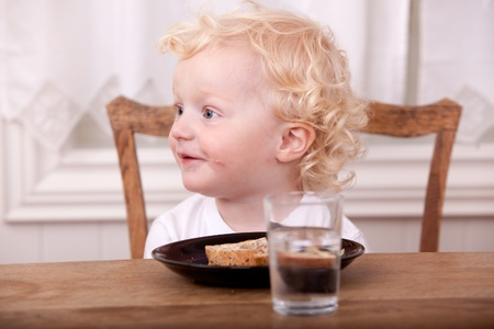 A young boy at the lunch table, looking off camera and smiling photo