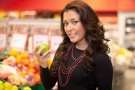 Portrait of a young woman holding apple in the supermarket photo