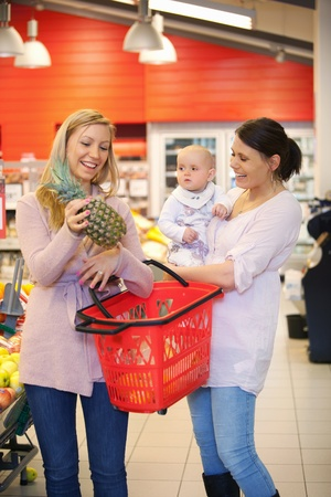 Mother and child with friend smiling while shopping in supermarket photo