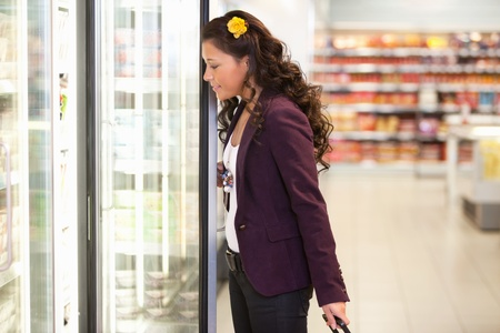 Young woman opening refrigerator in the supermarket photo