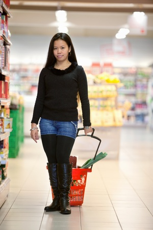 Full length of woman holding shopping basket in shopping centre and looking at camera photo