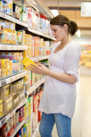 specifies: Woman takes a product from shelves at a supermarket