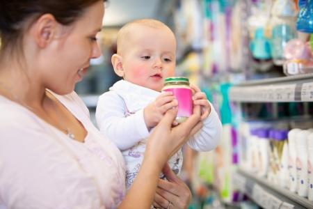 superstore: Mother shopping with baby in a supermarket, shallow depth of field - focus on baby Stock Photo
