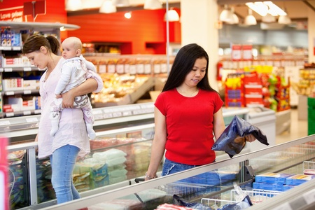 Woman and baby in grocery store with another female in foreground photo