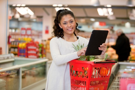 A happy woman using a tablet computer for a grocery list in a supermarket photo