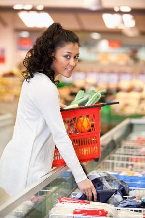 Young smiling woman buying frozen food in grocery store photo