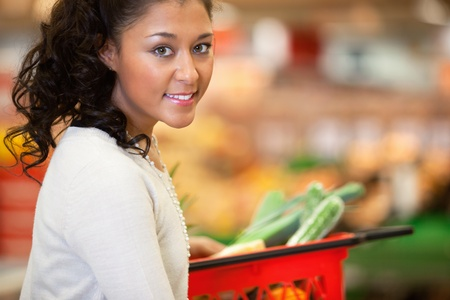 Close-up of young woman with red basket in supermarket and looking at camera photo