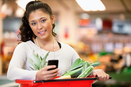 grocery trade: Smiling young woman using mobile phone while shopping in shopping store and looking at camera Stock Photo