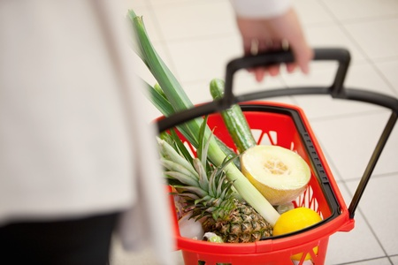 High angle view of human hand carrying red basket filled with fruits and vegetables photo