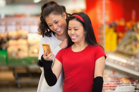 Smiling young women using mobile phone in shopping centre photo
