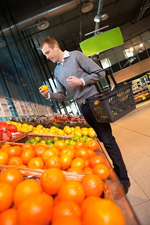 Man carrying basket while buying fruits in the supermarket photo