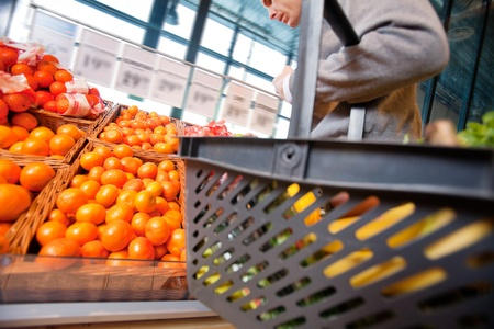 Closeup of a man carrying basket while buying fruits in the supermarket Stock Photo - 9886977