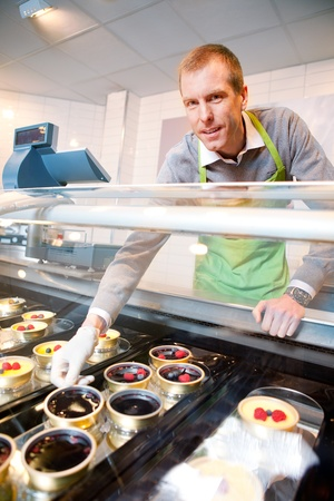 refrigerator with food: A store clerk selling fancy deserts from a glass counter