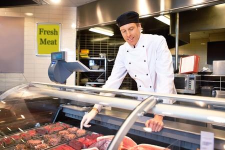 carniceria: Carnicero en un mostrador de carne fresca, ayudando a los clientes