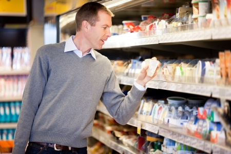 happy shopper: A man buying cheese and comparing prices in a grocery store