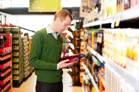 beverage display: A male shopper in a grocery store comparing products