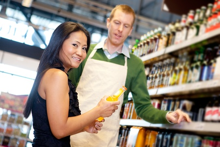 An asian woman in a grocery store receiving help from a store clerk photo