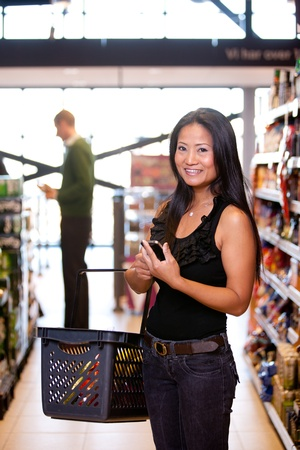 Portrait of a happy asian woman in a supermarket with a smart phone shopping list photo