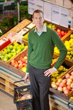 Serious man with hand on hip looking at camera while shopping in a fruit store photo