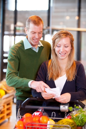 A happy couple looking at a grocery list in a supermarket Stock Photo - 9887023