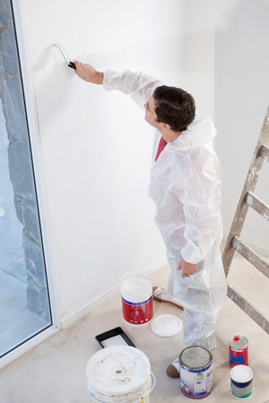 High angle view of workman painting the wall with a roller photo