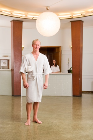 A man wearing a bathrobe in a day spa looking at camera photo