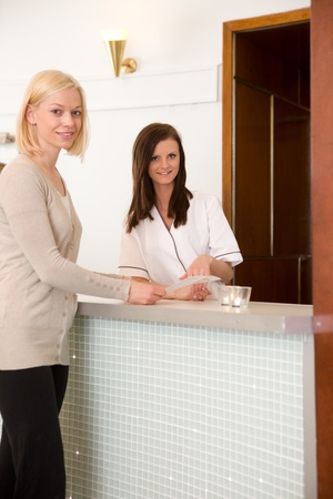 A woman choosing a therapy package in a spa.  Shallow depth of field, critical focus on spa receptionist photo