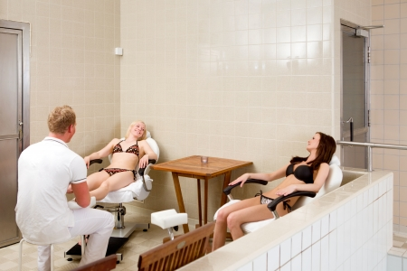 Two women receiving a pedicure and foot massage at spa photo