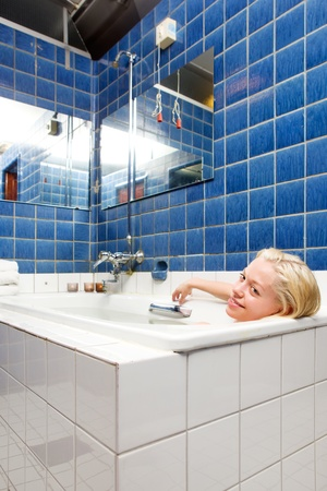 A woman taking a luxury bath cure in a old 20s style spa photo