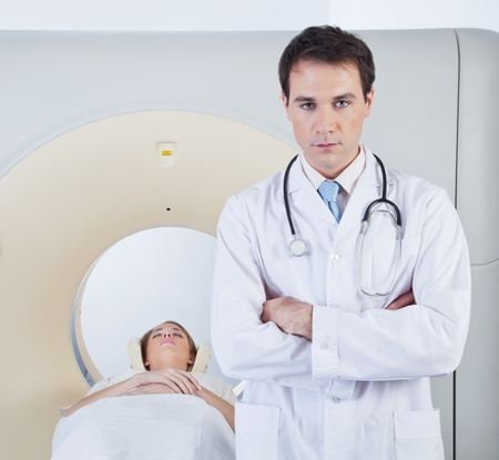 Serious doctor looking at camera in front of ct scanner photo
