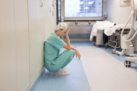 Müde Arzt sitzt allein im Flur