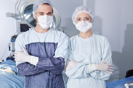 Portrait of young confident surgeons in operation theatre photo