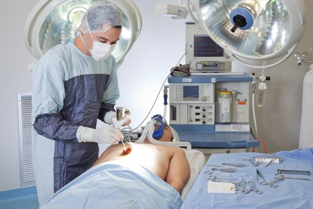 operations: Male doctor performing operation on patient in operating room Stock Photo